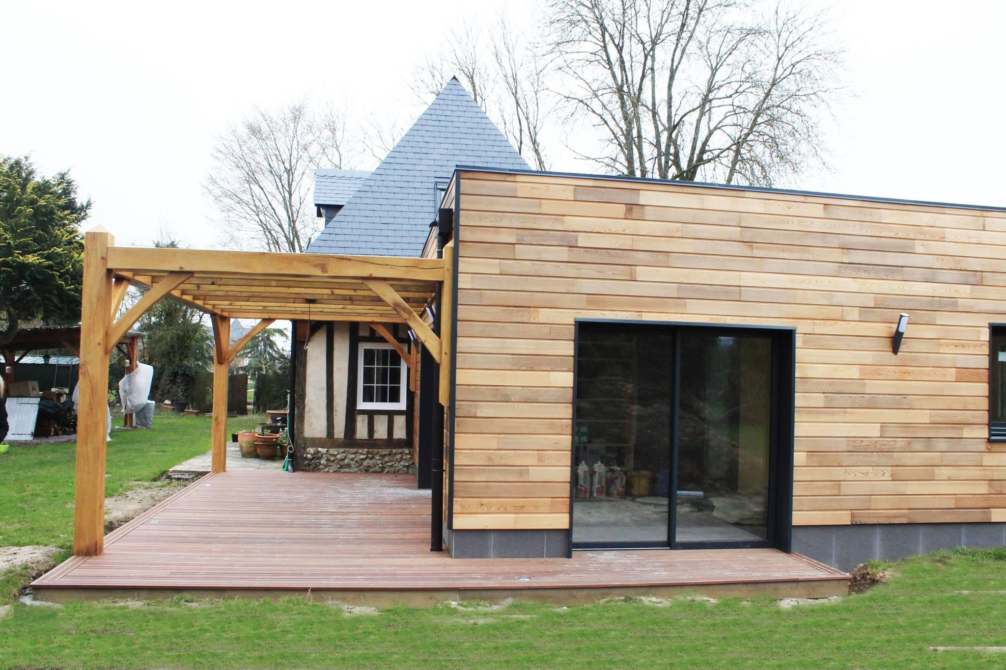 Réalisation d'une extension ossature bois de 70 m2 habitable sur une longère Normande. Construction de style moderne avec son bardage en Red Cedar, ses menuiseries aluminium, et terrasse en bois exotique sous pergolas